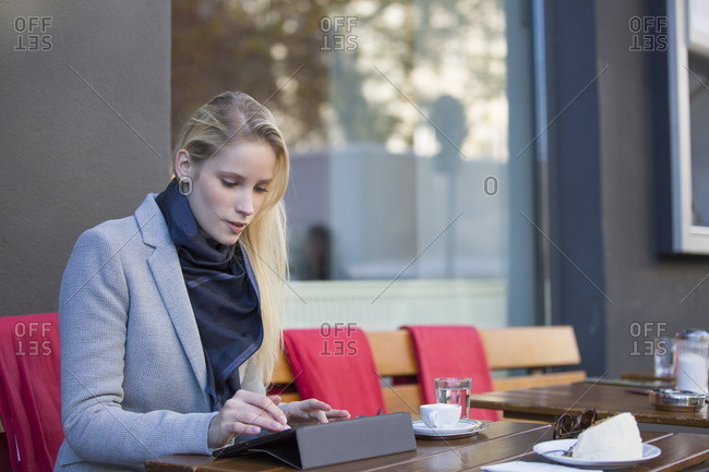 Pretty blonde woman with tablet in a Cafe