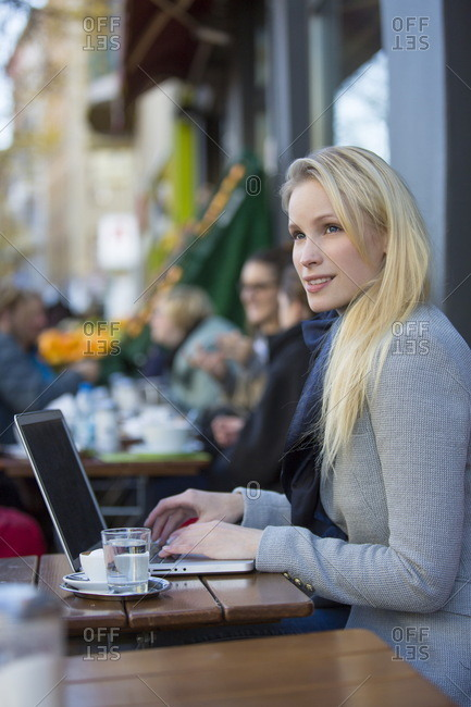 Pretty pensive woman with laptop in a cafe