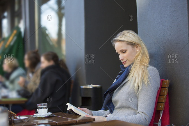 Pretty blonde woman reading a book in a Cafe in downtown