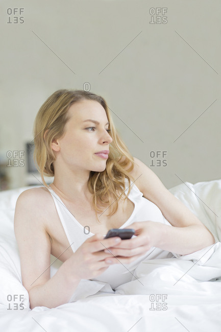 Pensive pretty woman with mobile in bed