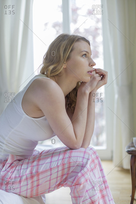 Serious and confused woman sitting on the bed