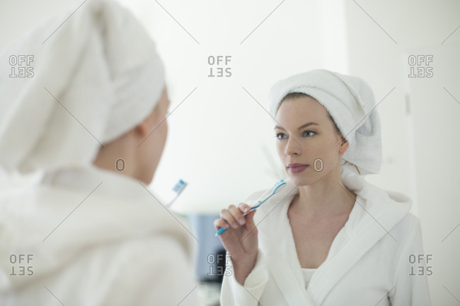 Woman in bathrobe brushing her teeth in front of the mirror