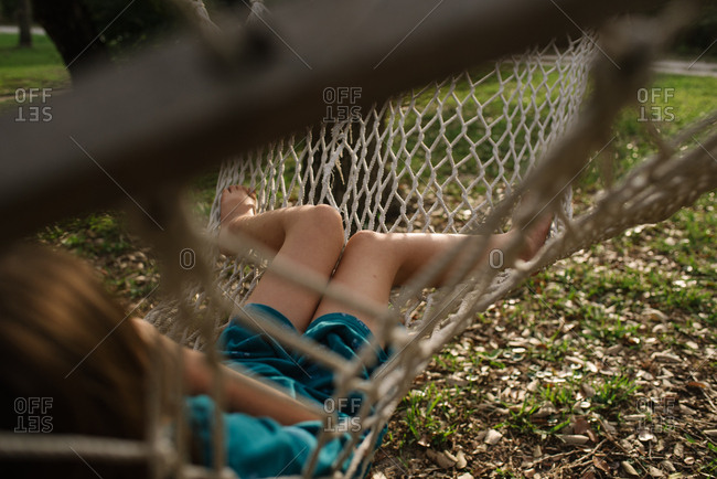 Girl swinging in backyard hammock