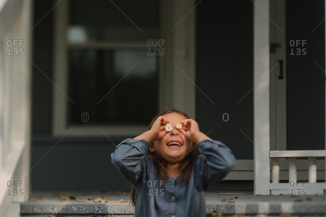 Little girl holding daisies in front of her eyes