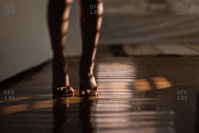 Barefoot child walking on hardwood floors
