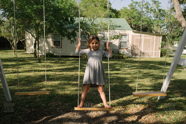 Little girl standing on backyard swing