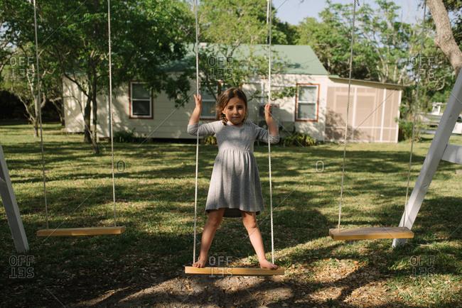 Little girl standing on backyard swing