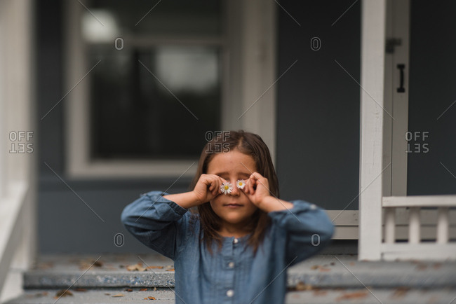 Girl holding daisies in front of her eyes