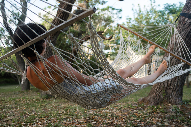 Woman relaxing in backyard hammock