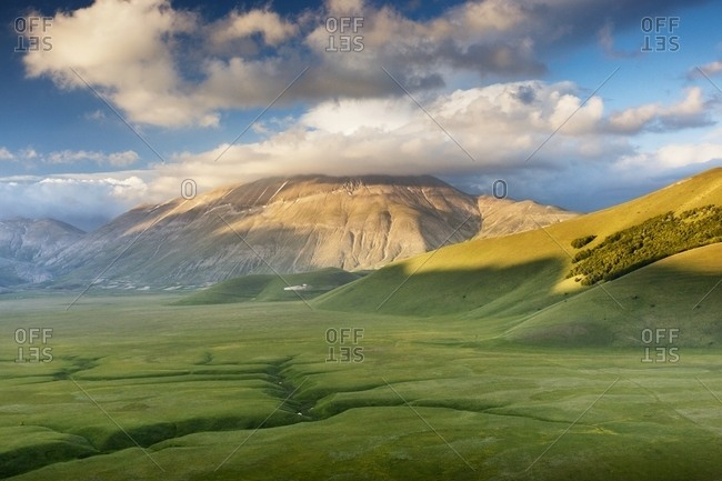 Last lights on Piano Grande Plateau with visible the karst Fosso dei Mergani and in the background Vettore Mount and its fault, Sibillini National Park, Italy