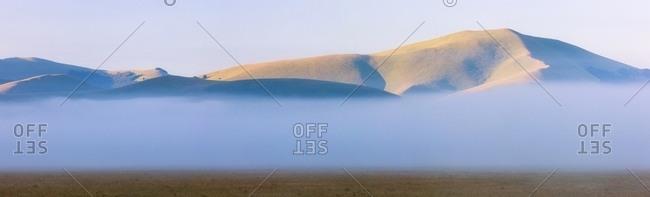 Fog and clouds at dawn on Sibillini meadows, Castelluccio di Norcia, Sibillini National Park, Italy
