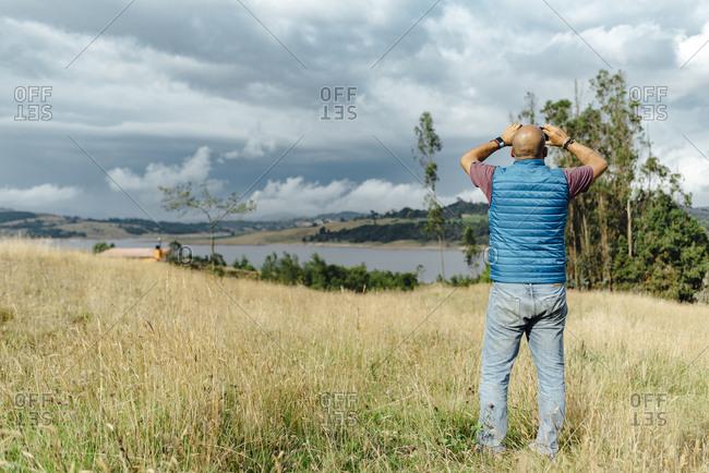 Middle-aged man taking a picture of Guatavita lake in Represa del Sisga, Colombia