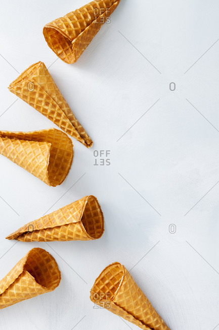 Ice cream cones scattered on a white background