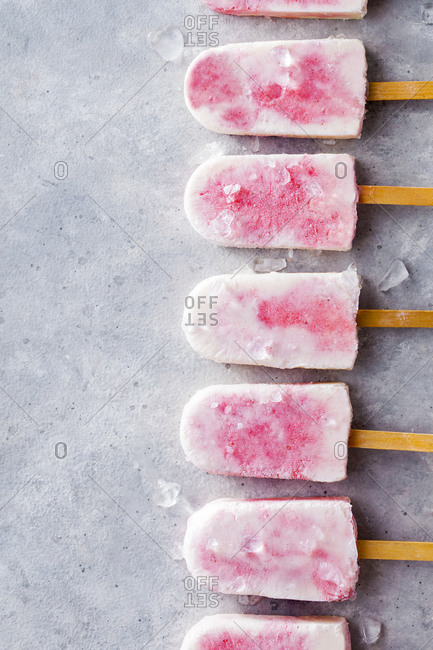 Raspberry yogurt popsicles arranged on top of ice cubes