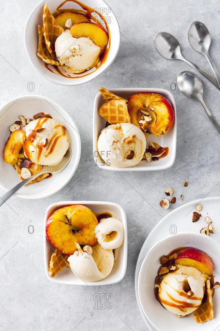 Scoops of vanilla ice cream with fruit, nuts and caramel drizzle