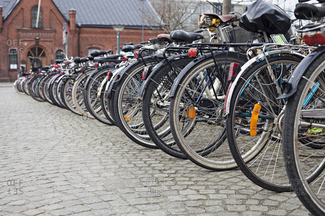 Row of bicycles parked on cobblestone street in Aarhus, Denmark