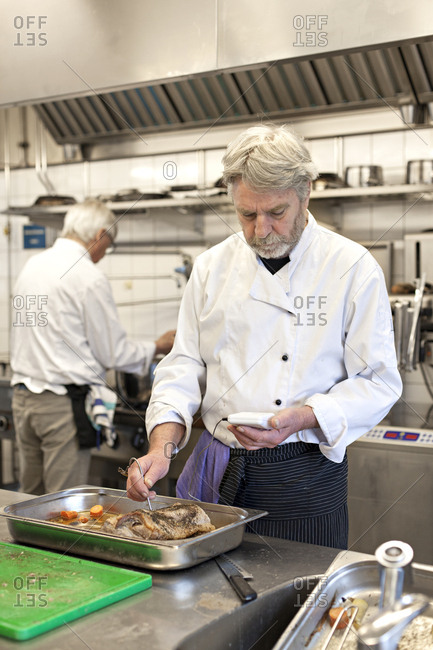 Male chef checking temperature of food in a restaurant kitchen