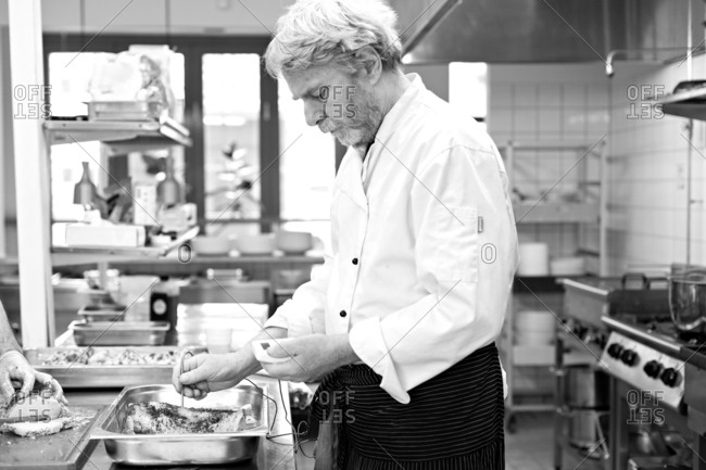 Male chef checking temperature of food in a restaurant kitchen in black and white