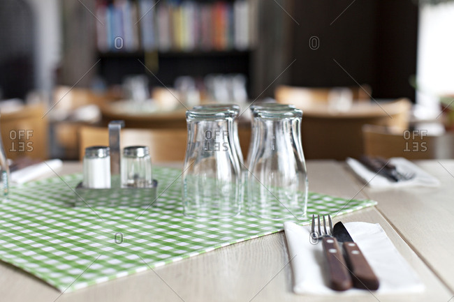 Glasses and silverware on a set table in a restaurant