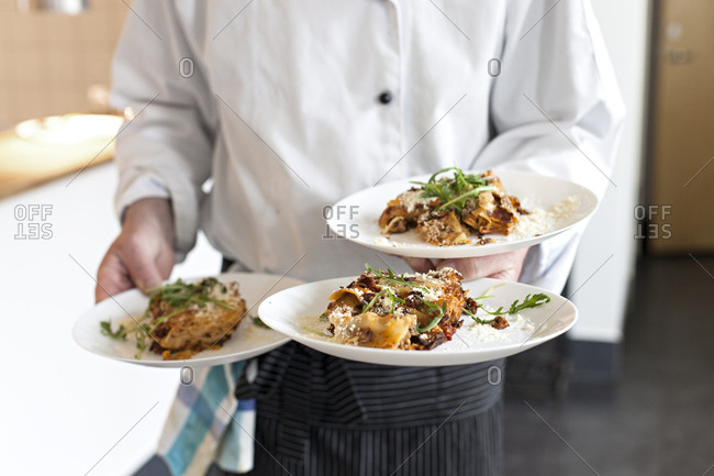 Server carrying three dishes in a restaurant