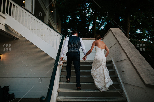 Bridal couple going up stairs at dusk