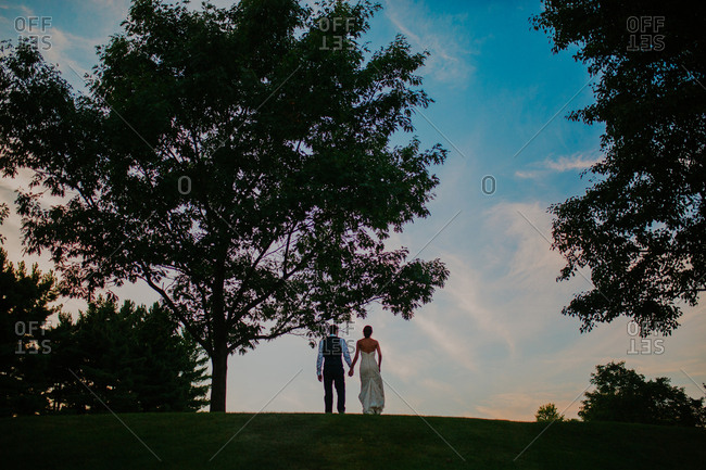 Bride and groom at top of a hill