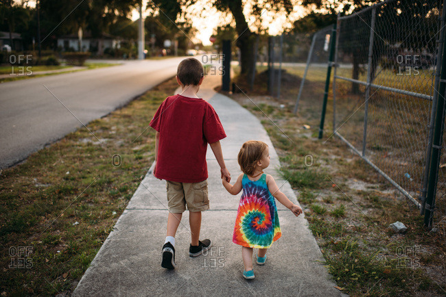 Big brother and little sister holding hands walking down a suburban sidewalk