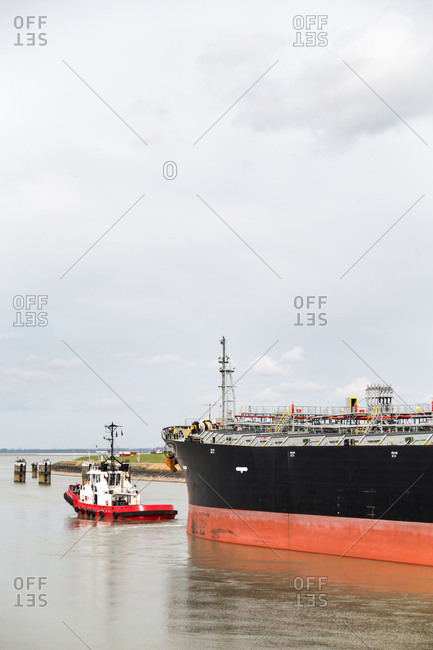 Tug boat guiding freight ship