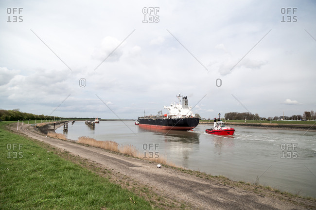 Tug boat guiding freight ship in canal