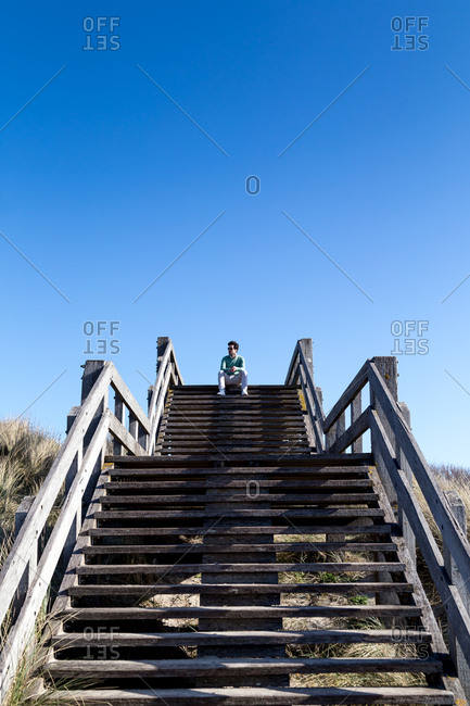 Young man sitting on coastal steps