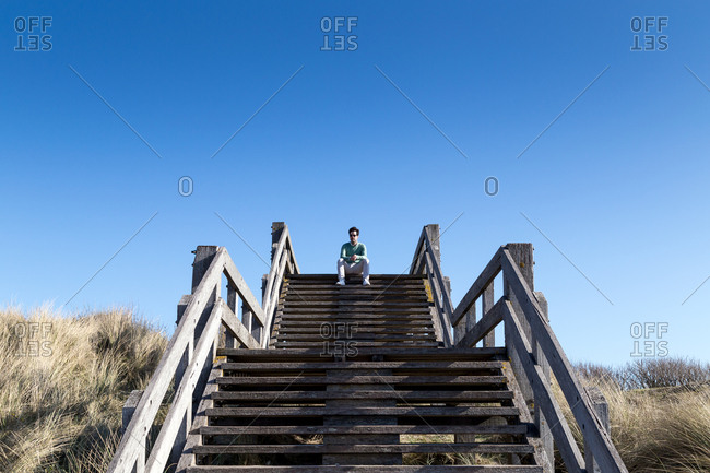 Young man sitting on coastal stairs