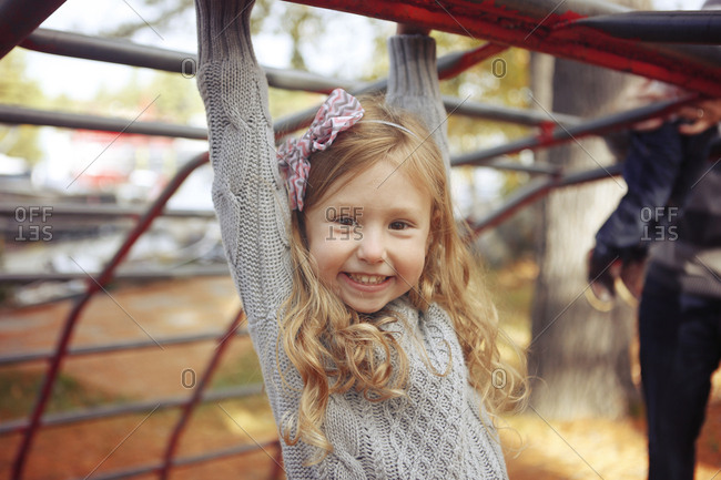 Young girl with bow in her hair swinging from monkey bars