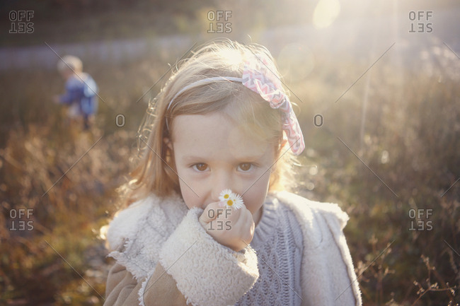 Young girl smelling small flowers in a sunny field