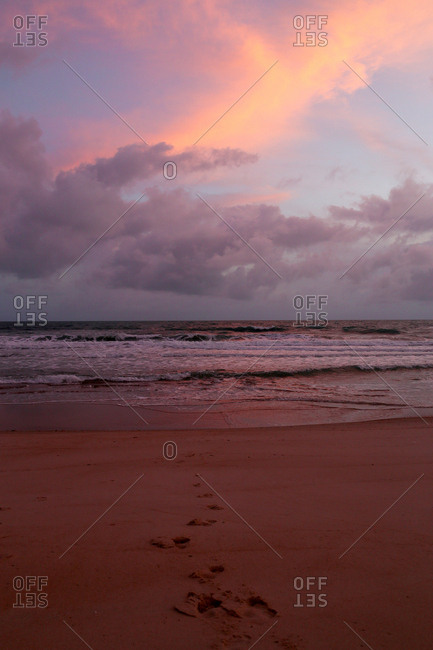 Sunset over sandy beach and waves with footprints