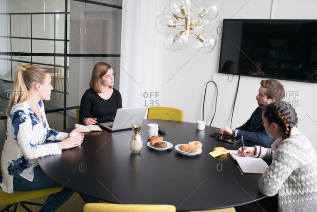 Four people sitting at a table having a meeting together