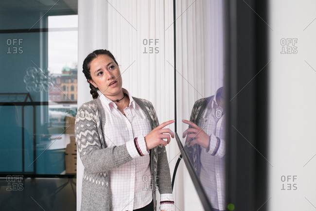 Businesswoman pointing at screen during meeting