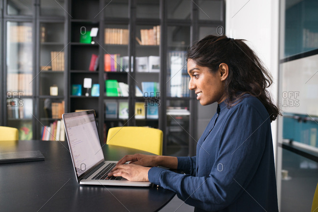 Smiling young businesswoman typing on a laptop computer