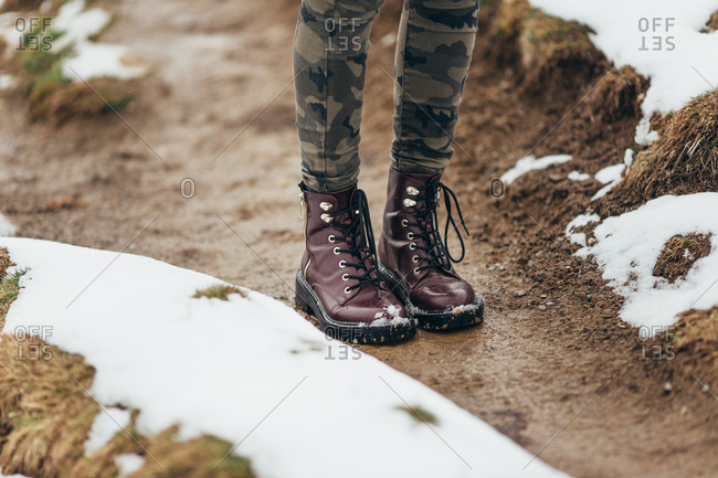 Close Up Of Woman Wearing Brown Leather Boots In Snow Stock Photo