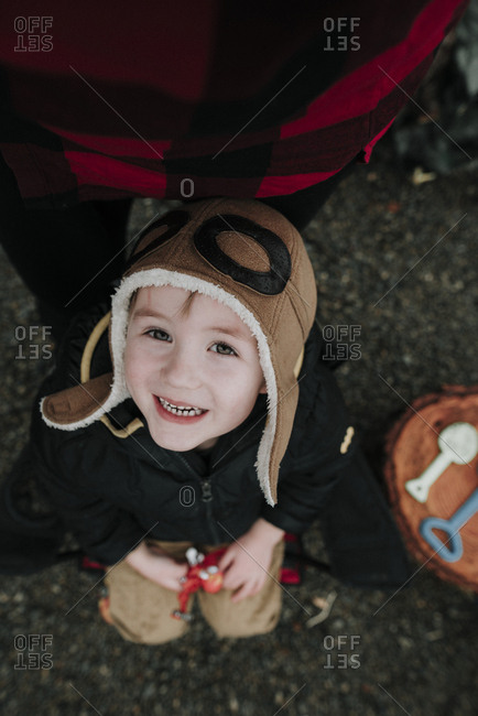 Little boy in an aviator hat looking up an smiling