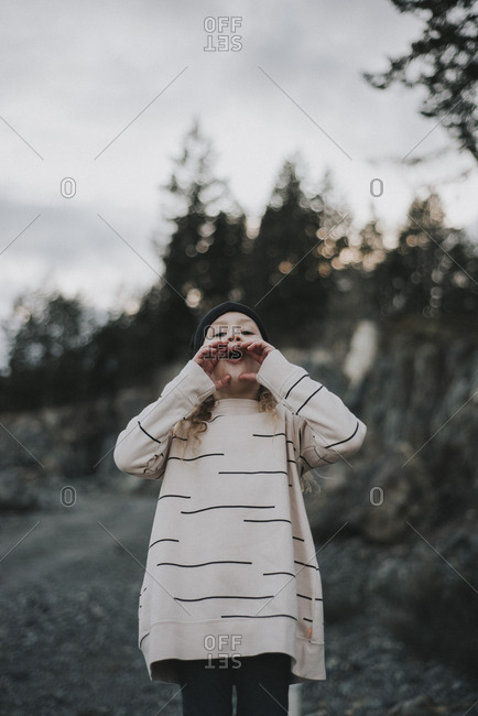 Girl standing outdoors cupping her hands around her mouth and howling
