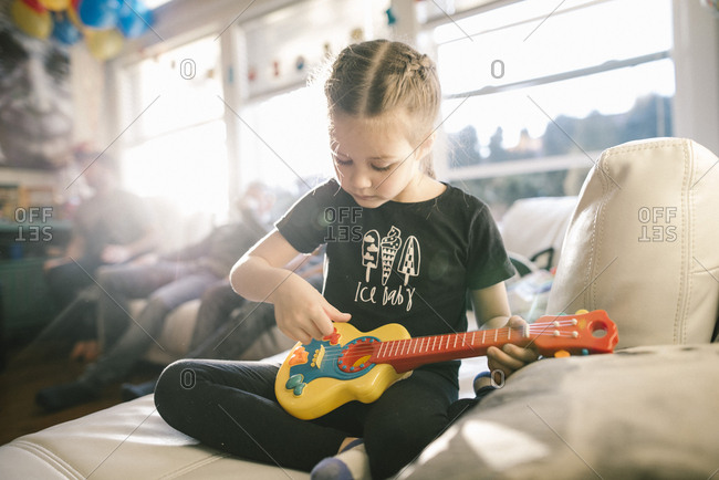 Little girl sitting on a sofa playing a toy guitar