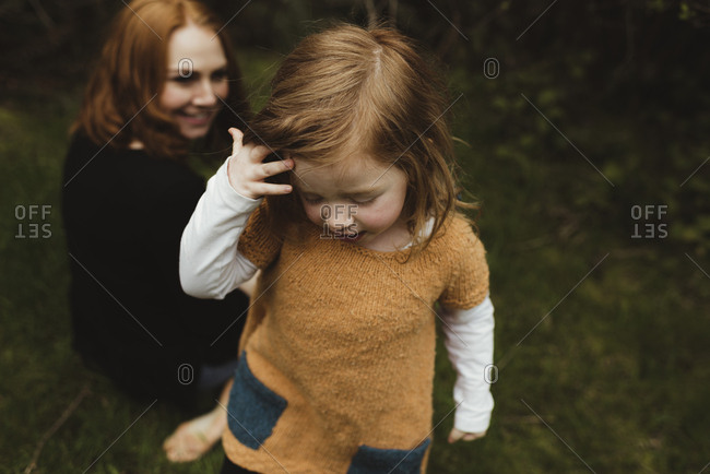 Little girl standing in a field with her mother