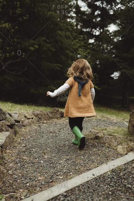 Little girl walking on a gravel trail
