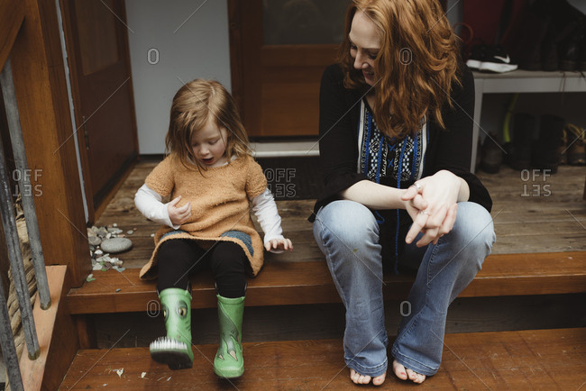 Mother and daughter sitting on porch steps together