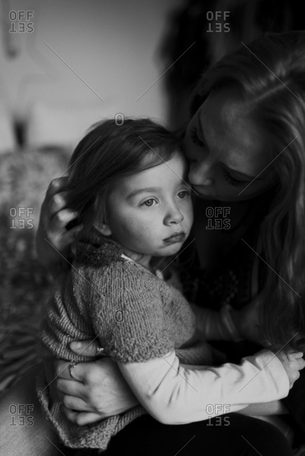 Mother holding her daughter in her lap and consoling her