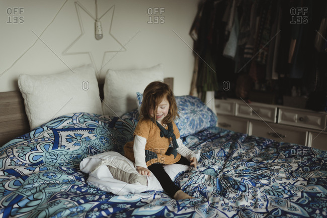 Little girl sitting on a bed smiling
