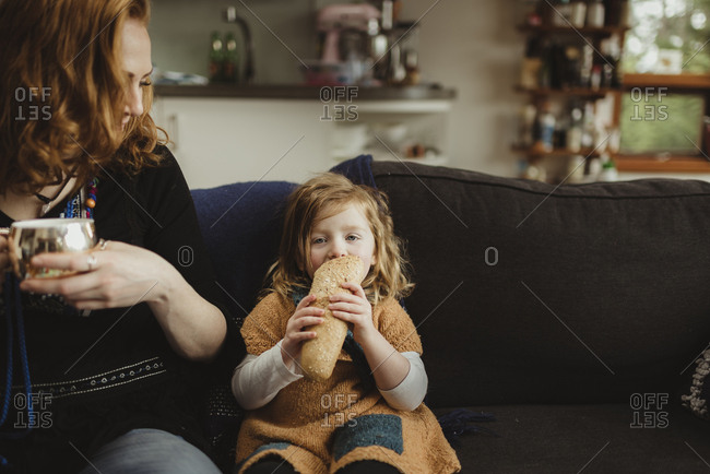 Girl sitting on a sofa eating bread next to her mother