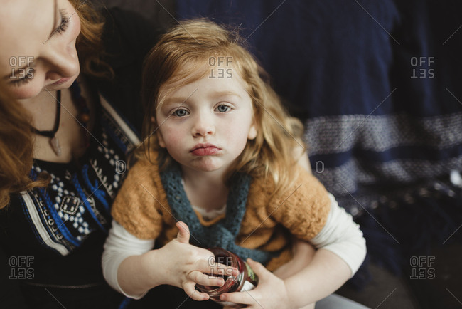 Little girl sitting in her mother's lap holding a jar of jam