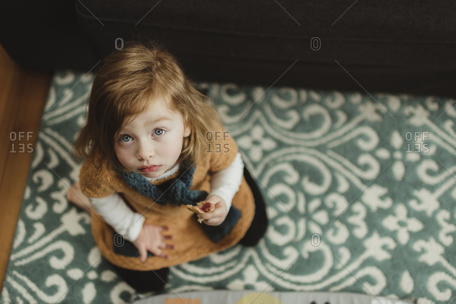 Little girl on a blue patterned rug holding a piece of toast