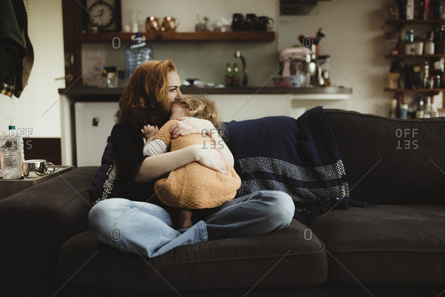 Mother embracing and consoling her daughter on a sofa